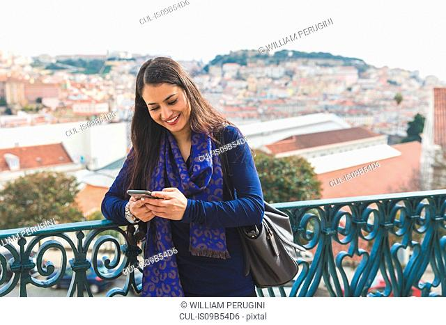 Woman texting on smartphone, Lisbon, Portugal