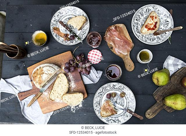Lunch with bread, grapes, pears, cups of tea, marmelade and jambon