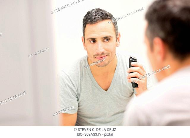 Mid adult man, looking in mirror, using electric shaver