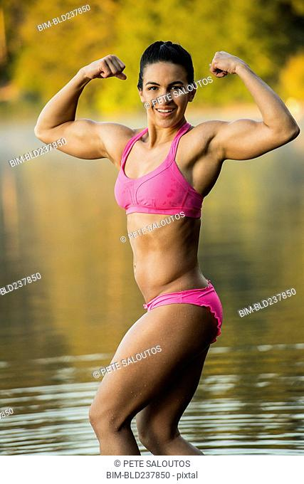 Mixed Race woman flexing muscles in lake