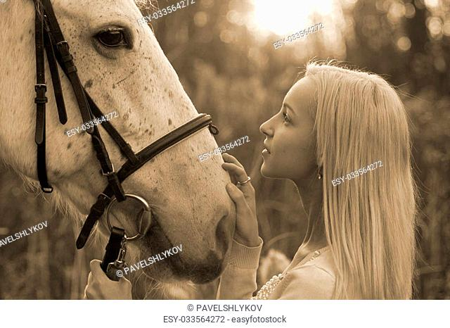 Blonde and white horse looking into each other's eyes on sundown in sepia