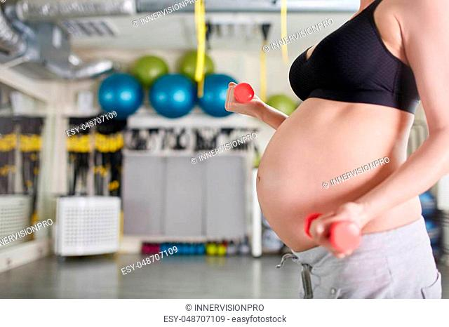 Cropped side portrait of pregnant woman lifting weights at gym