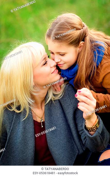happy mother and daughter in the autumn forest, walking and hugging