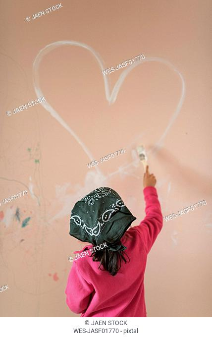 Back view of little girl painting heart on wall of children's room