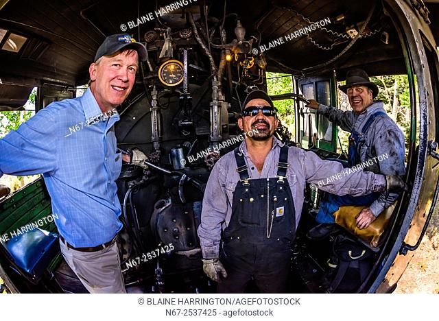 Colorado Governor John Hickenlooper riding in the steam locomotive with the train engineer and fireman during a visit to the Cumbres & Toltec Scenic Railroad...