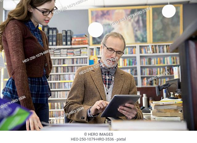 Woman watching bookstore owner using digital tablet