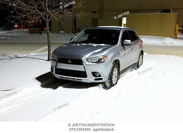 car parked in deepening snow in outdoor parking lot in Saskatoon Saskatchewan Canada