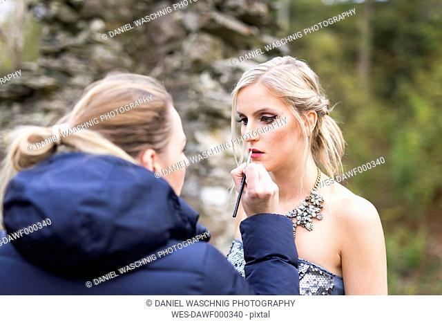 Female visagiste applying lipstick on young woman's lips