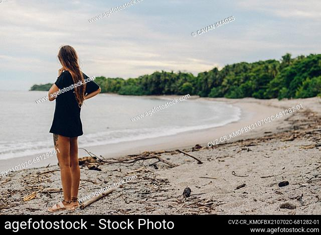 a lonely girl looking around in a beautiful beach in costa rica