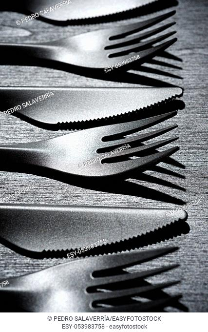 Disposable plastic cutlery on a black table