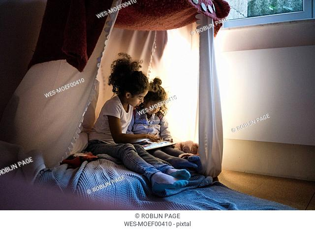 Two sisters sitting in dark children's room, looking at digital tablet