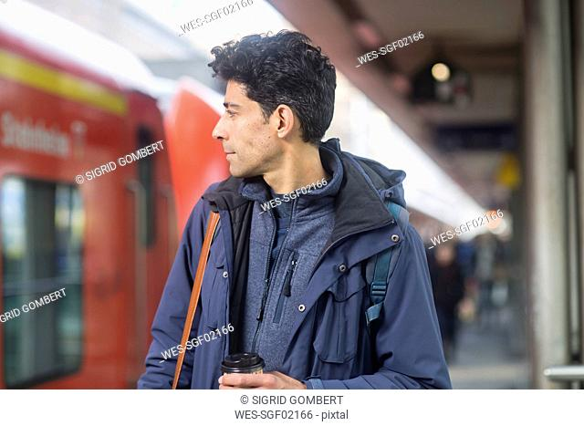 Man with backpack and coffee to go on platform