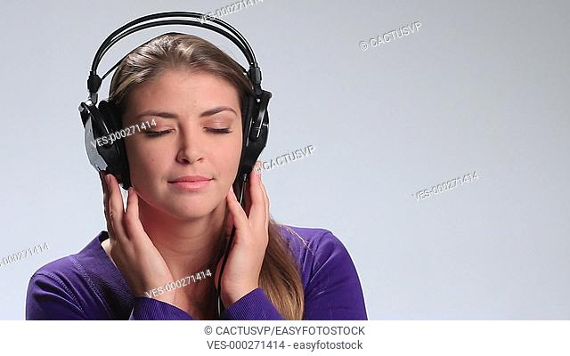 Calm brunette woman enjoying music in headphones
