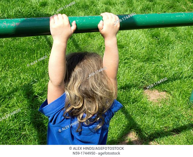 Young child hanging from a climbing frame