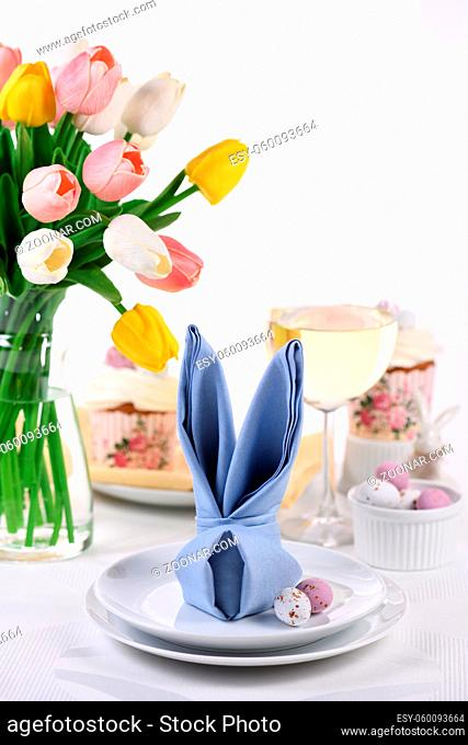 A napkin folded in the shape of a hare (rabbit), the concept of setting a festive table in honor of Easter