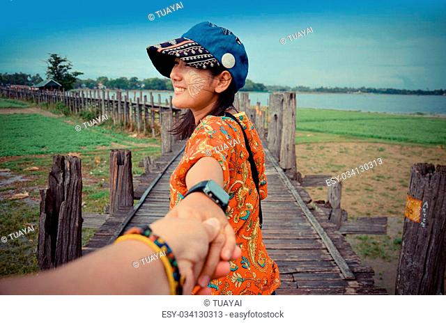 Thai woman lead someone by the hand and hold on the walkway