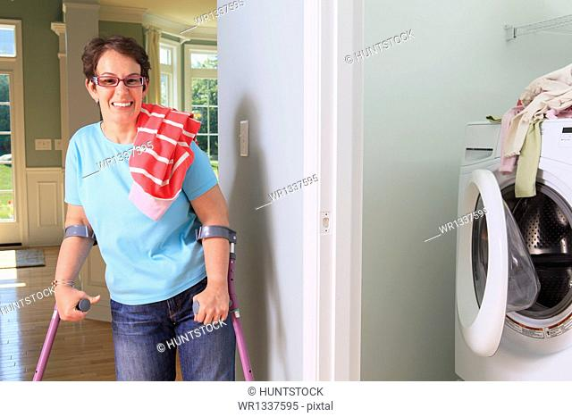 Woman with cerebral palsy washing clothes in the laundry room and smiling