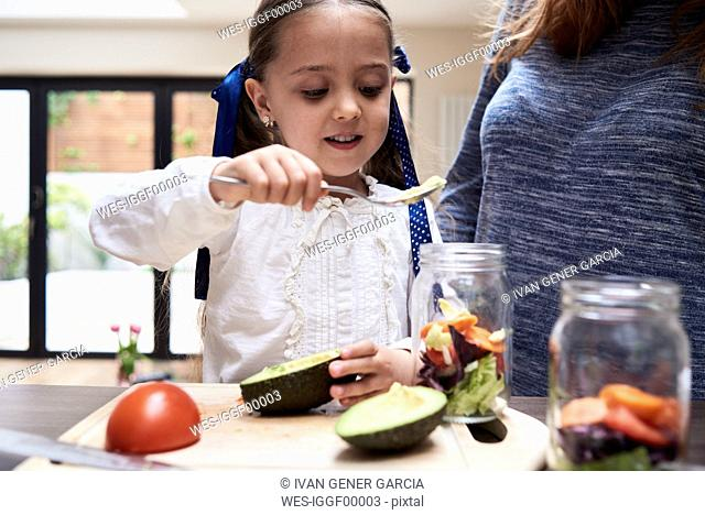 Portrait of little girl preparing healthy salad with her mother in the kitchen