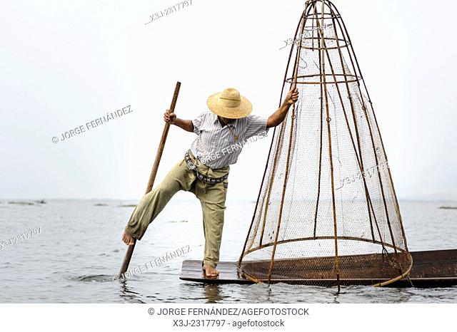 Inle Lake fisherman rowing with his feet, the traditional way to do so in the area, Inle lake, Myanmar, Asia