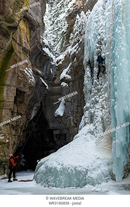 Male rock climber climbing ice mountain
