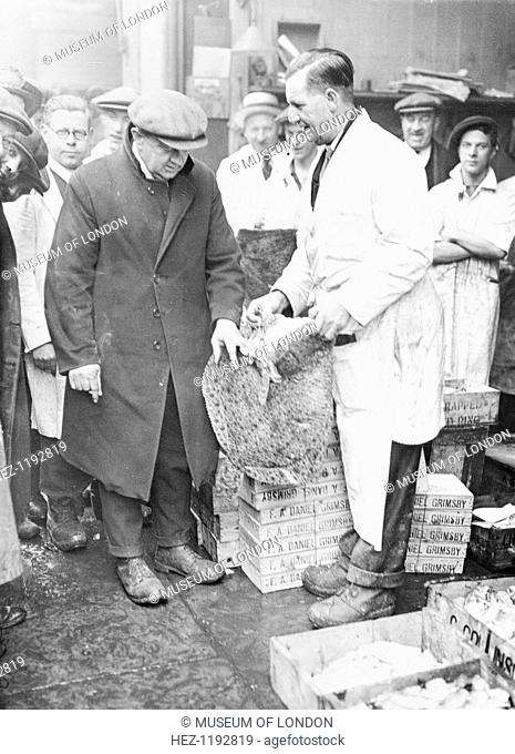 Man choosing fish at Billingsgate Market, City of London, (c1930s?). A buyer selecting turbot at the famous fish market. The boxes are marked 'Grimsby'