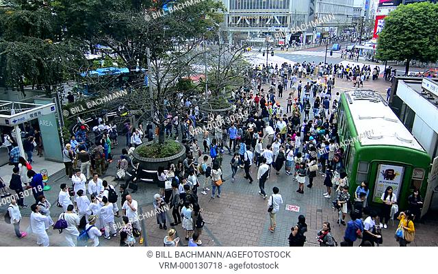 Tokyo Japan crowds rush moving walking in the busy Shibuya Station area of Shilbuya Crossing with locals rushing everywhere in downtown crowded streets and...