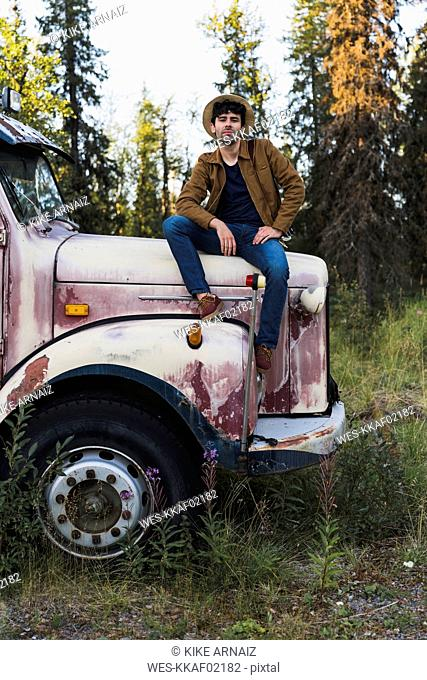 Cool young man sitting on a broken truck