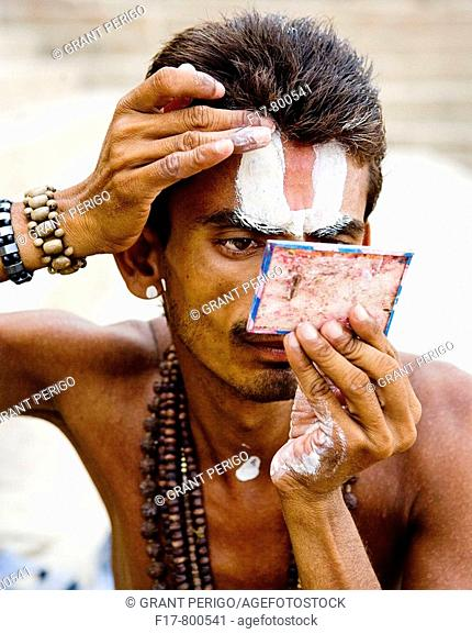 picture of a priest applying makeup by the ganges river