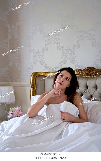 Young woman in bed looking puzzled