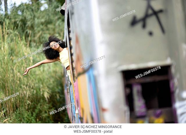 Happy young woman leaning out of abandoned and destroyed old train