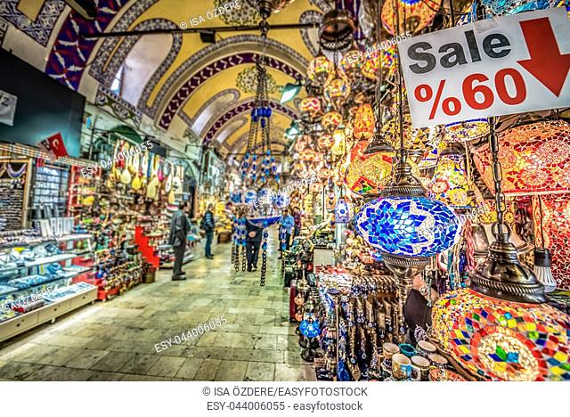 Unidentified people visiting the Grand Bazaar for shopping,. Interior of the Grand Bazaar with traditional handmade decorative mosaic multi-colored Turkish...