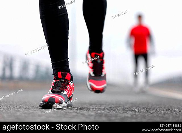 Running shoes - closeup of male runners running on winter street. Sport fitness athlete man jogging outdoors on city road in cold weather