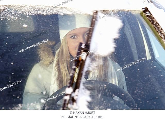Woman wiping snow out of windscreen