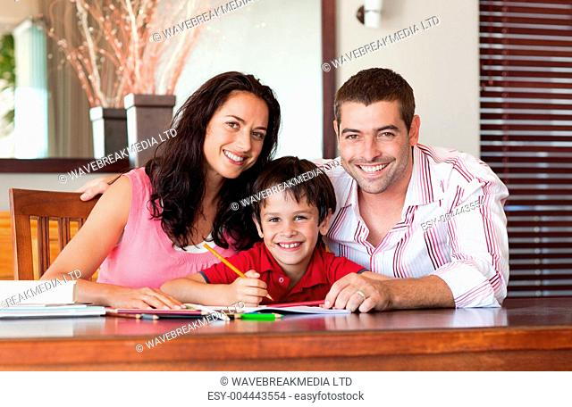 Smiling couple helping his son for homework