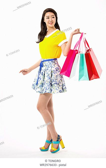 Young smiling woman in casual clothes with shopping bags posing