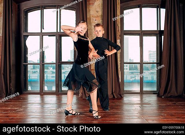 Young couple boy and girl dancing in ballroom dance Rumba