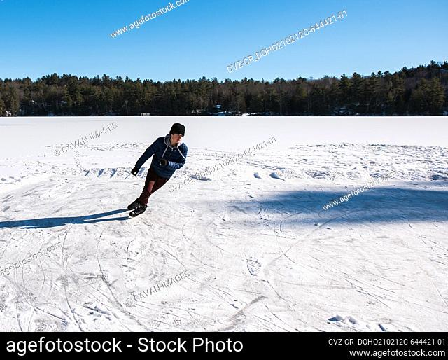 Teen boy ice skating on a frozen lake on a winter's day in Canada