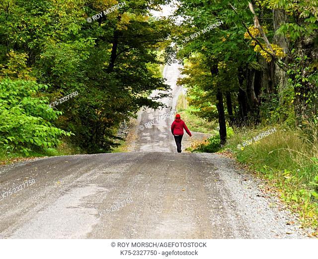 Woman walking country road at the beginning of autumn. Pocono Región, Pennsylvania, USA