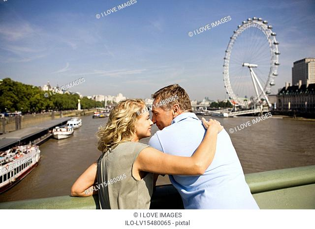 A middle-aged couple standing near the London Eye, embracing