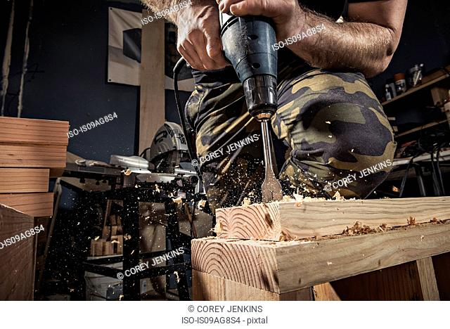 Close up of male carpenter drilling wooden plank in workshop