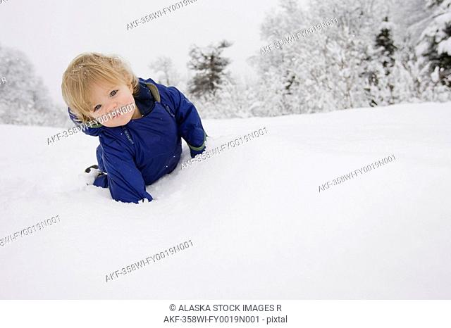 Young boy on a winter walk in Pedro Bay, Alaska
