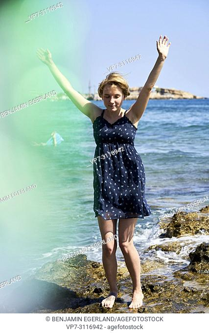woman at beach, sensual, enjoying warm summer breeze, in holiday destination Chersonissos, Crete, Greece