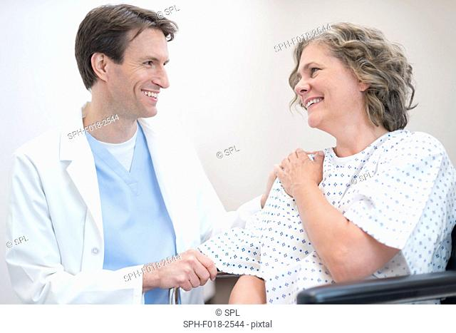 Male doctor smiling at mature female patient