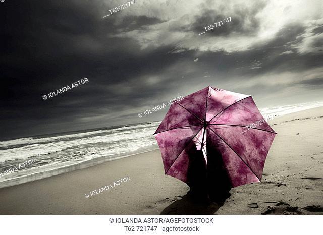 Mujer con paraguas sentada en la playa tras la tormenta