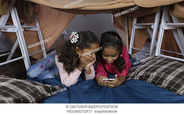 Little girls with phone browsing social networks