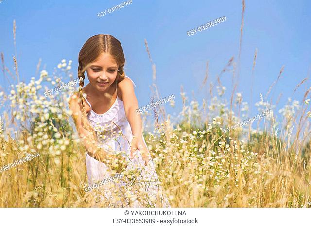 Pretty girl is picking flowers on field. She is standing and laughing