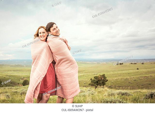 Portrait of young couple on hilltop wrapped in pink blanket, Cody, Wyoming, USA