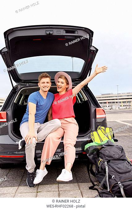 Portrait of happy young couple in a car at the airport