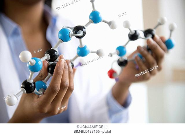Mixed race scientist examining molecular model