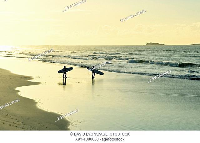 Surfers carrying surfboards walking along sandy beach shoreline evening light summer  White Rocks Strand, Portrush, Ireland